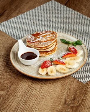 pancakes with sliced fruits and jam