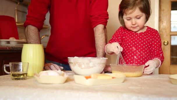 Ein kleines Mädchen in roter Kleidung backt Kuchen aus Mehl, zu Hause in der Küche, während der Quarantäne