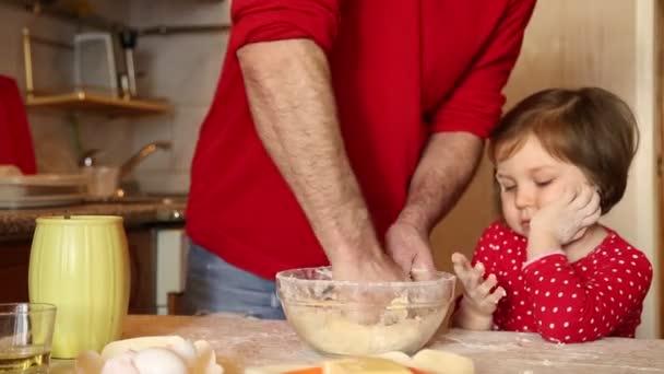 Egy vörös ruhás kislány lisztből készít süteményt, otthon a konyhában, a karantén alatt.