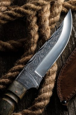 Hunting knife handmade with patterns on the old wooden backgroun