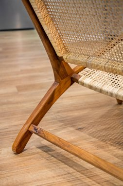 Detail of back part of modern wicker chair standing in a living room with laminate. Interior wooden furniture.