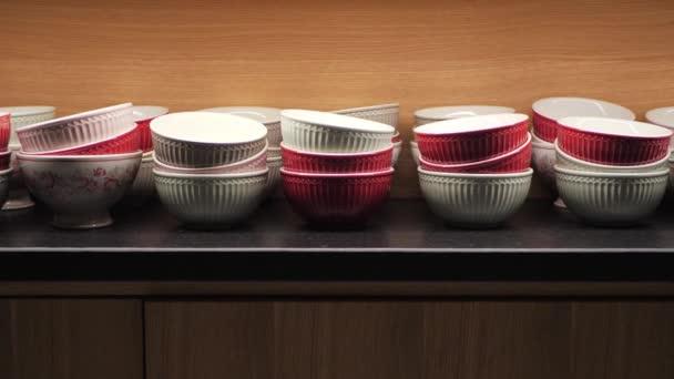 Červené a bílé keramické misky v dřevěné kuchyňské skříni. Stolní nádobí osvětlené shora ve skříni moderního interiéru