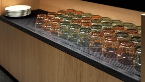 Sideboard baru nebo restaurace s průhlednými sklenicemi na pití vody nebo džusu a bílých talířů