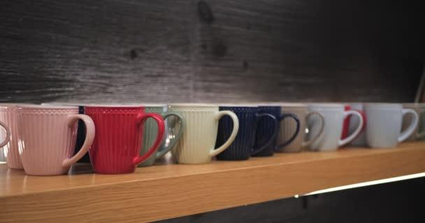 Šálky různých barev na dřevěné kuchyňské polici s černým kamenným pozadím. Zaměření přechodu.