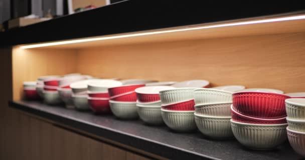 Červené a bílé keramické misky v dřevěné kuchyňské skříni. Zaměř se. Stolní nádobí osvětlené shora ve skříni, moderní vnitřní vitrína.