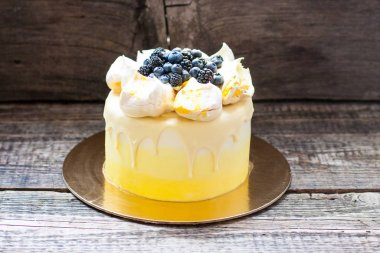 Yellow vanilla and lemon cake with meringues and fresh grapes, blueberries, blackberries.