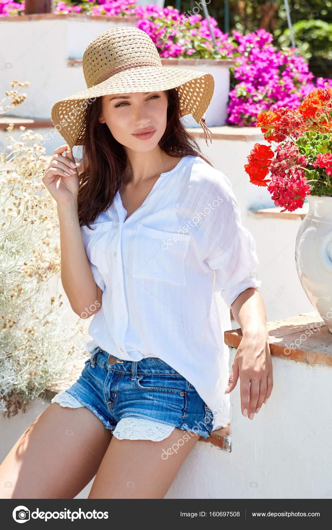 Mujer bonita joven sonriendo. Mujeres hermosas en un sombrero de paja en el  jardín de verano — Foto de BellaStudio 2fb592733ec