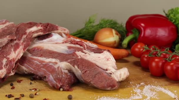 fährt die Kamera an einem großen Stück rohem Rindfleisch mit Fett und verschiedenen Gemüsesorten vorbei, Seitenansicht, Nahaufnahme