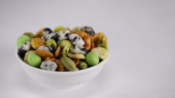 Japonské horké svačinky s arašídy, hráškem a wasabi leží v bílé míse v popředí, v pozadí ženské ruce dát na stůl další dva poháry s dalšími japonskými svačinkami
