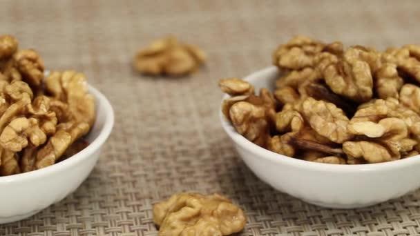 Tři bílé misky s vlašskými ořechy stojí na šedém proutí povrchu