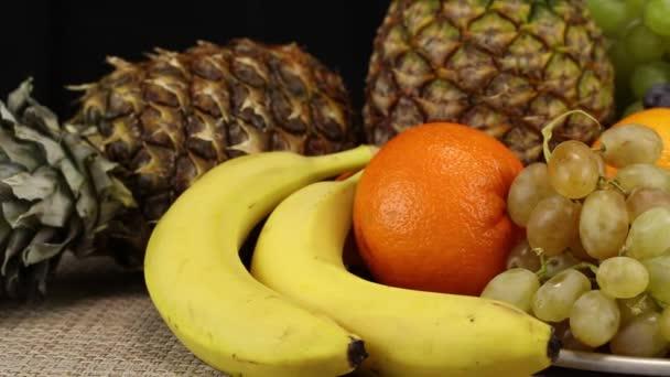 Sok különböző gyümölcs fekszik egy ezüst tálcán és egy szürke fonott felületen, közelről