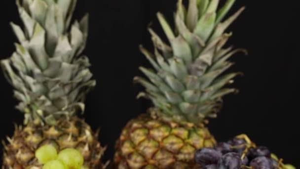 Két ananász, szőlő, gránátalma és banán fekszik egy ezüst tálcán, közelről.