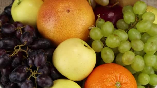 Apples, orange, grapes and kiwi rotate clockwise, top view