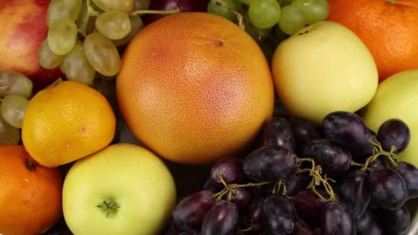 Sötét szőlő, grapefruit, alma, narancs és zöld szőlő forog az óramutató járásával megegyező irányban, felülnézet
