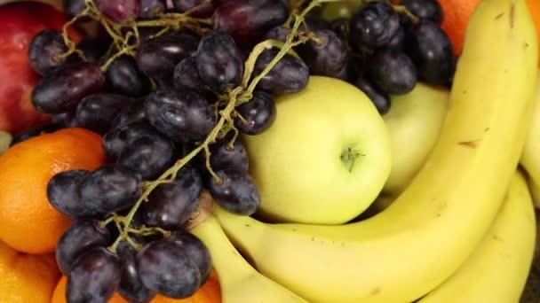 Tmavé hrozny, banány, jablka a pomeranče rotují ve směru hodinových ručiček, výhled shora, detailní záběr
