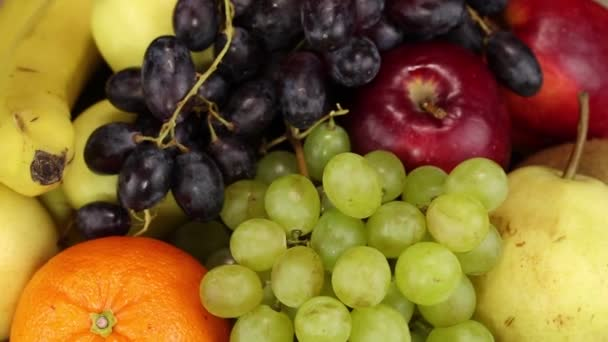 Orange, green grapes, pear, red apples and kiwi rotate clockwise, top view, close-up