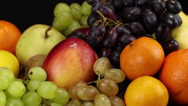Női kéz teszi narancs és mandarin egy nagy halom különböző gyümölcsök