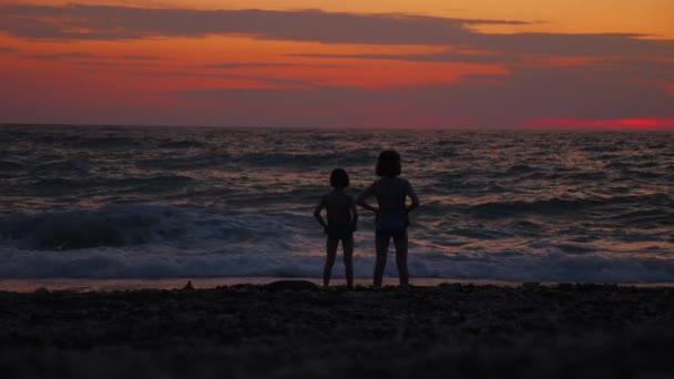 Due bambine si affacciano sul mare o sulloceano al tramonto.