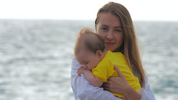 Mladá matka drží dítě v náručí, zatímco stojí u moře nebo oceánu.