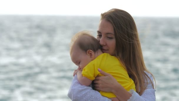 Young mother holds baby in her arms while standing by the sea or ocean.