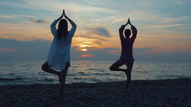 zwei junge Frauen praktizieren Yoga am Meer oder Meer bei Sonnenuntergang.
