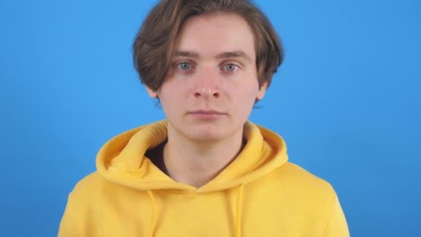 Mladý muž ve žluté mikině se dívá do kamery