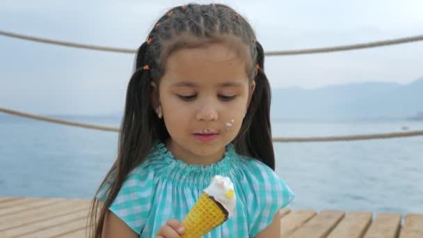Malá dívka olizuje zmrzlinu kornout na pozadí moře nebo oceánu.