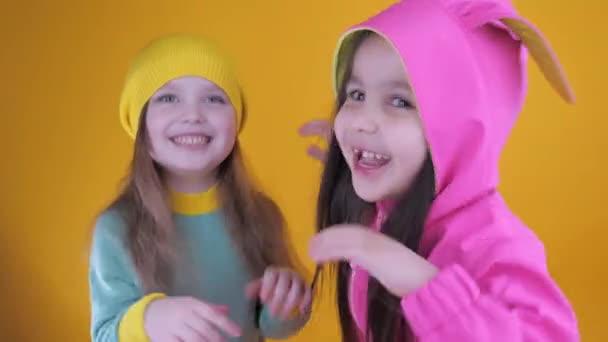 Két vidám aranyos kislány szórakozik a sárga háttér