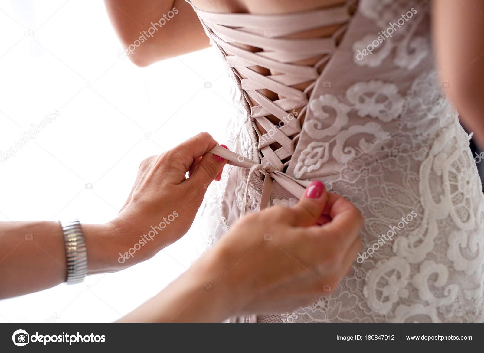 Brautjungfer Bogen auf Hochzeitskleid zu binden. Vorbereitung der ...