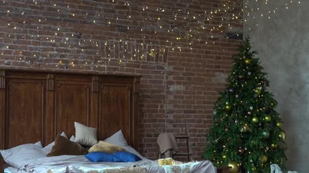 Stylový vánoční interiér, ložnice se spoustou světel. Pohodlný domov v podkrovním stylu s vyzdobeným vánočním stromečkem a věncem.