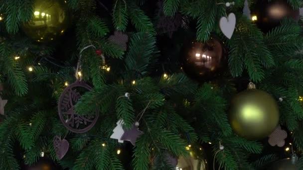 Közelkép a karácsonyfa részleteket dísztárgyak baubles, hópelyhek, arany golyók, szív alakú derokor és fények koszorúk