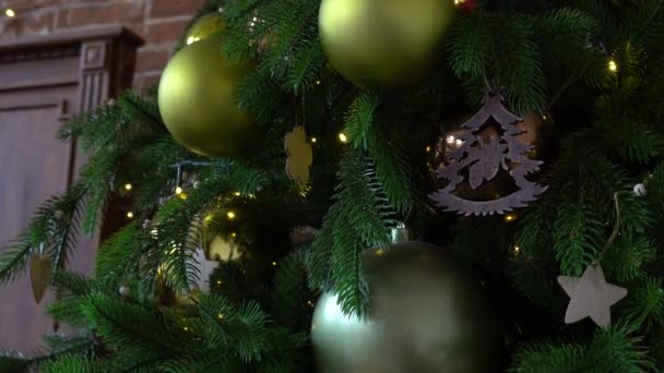 Detailní záběr na vánoční stromeček s ozdobou ozdoby cetek, sněhové vločky, zlaté koule, srdce ve tvaru derocor a světla věnce