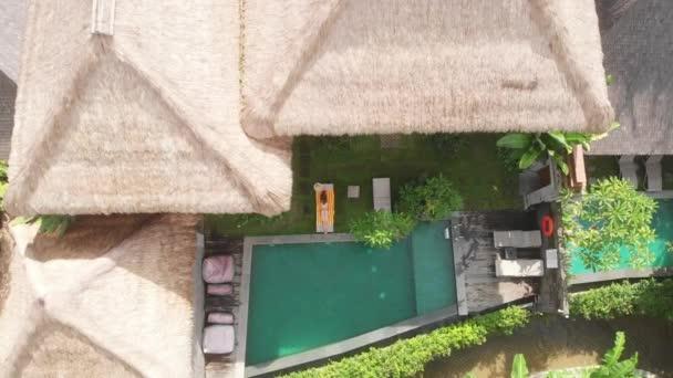 Légi felvétel vékony fiatal nő bézs bikini pihentető és kap napozó közelében medence chaise-longue trópusi kertben villa Ubud. A drón felszáll. Nyaralási koncepció.