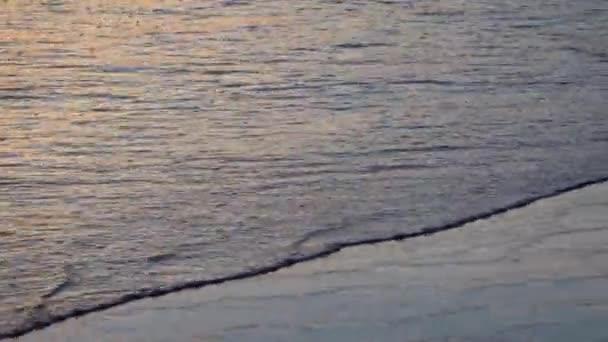Close up video vln s pěnou valící se po černé sopečné písečné pláži oceánu, Bali, Indonésie