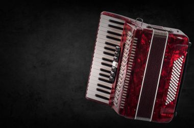 Red accordion on wooden grey background. Write text