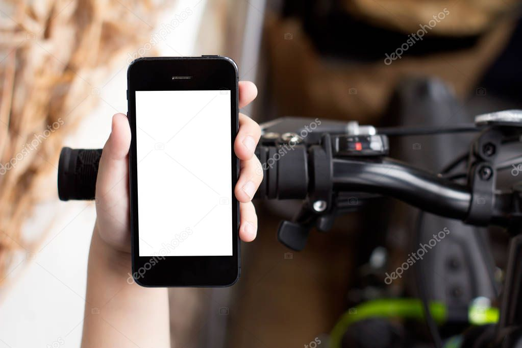 Boy's hand use smartphone while he stands near by the road with bikes