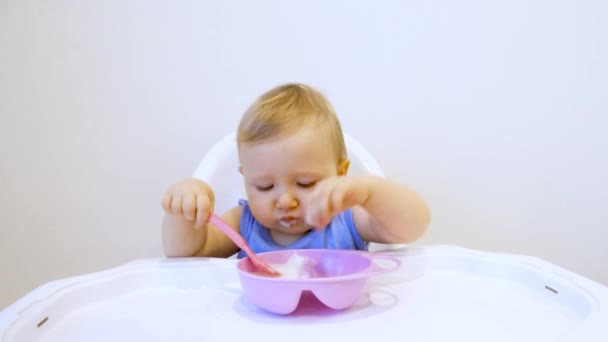 A child for the first time in his life eats porridge himself. The child eats for the first time on his own