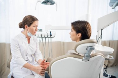 Female dentist discussing a report with her patient at the clini