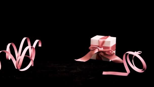 Dámská ruka umístění Dárek box s růžovou stuhou na růžovém a černém pozadí, Dovolená, Dárky, Kopírka, Pozdrav
