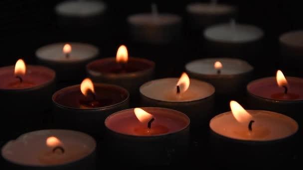 Detailní záběr hořící svíčky, seskupené na černém pozadí. Romantická atmosféra