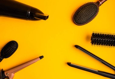 Professional hair dresser tools on yellow background with copy space, top view Set of hairdressers on bright background.