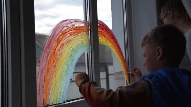Dívka a chlapec malovat duhu na okno během Covid-19 karantény doma. Zůstaňte doma kampaň sociálních médií pro prevenci koronavirů