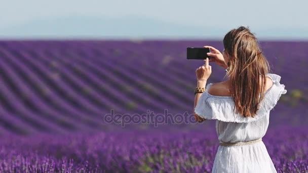 Frau mit Kamera auf Lavendelfeld