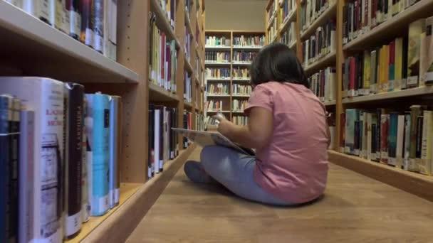 Mladá dívka čte komiks sedí na podlaze knihovny