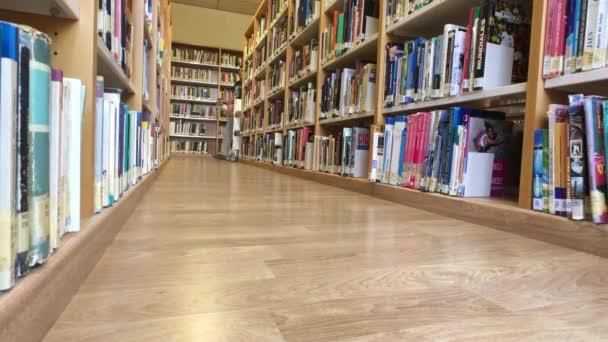 Muž středního věku vypadá a vyzvednout knihu v knihovně