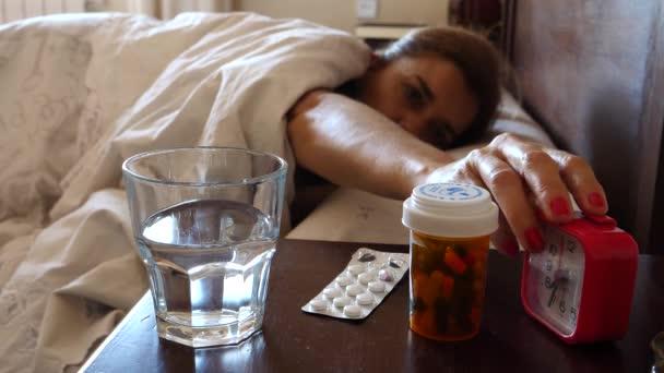 Nemocná v posteli probudí brát léky každý den, když budík zvuky, koncepční obrázek
