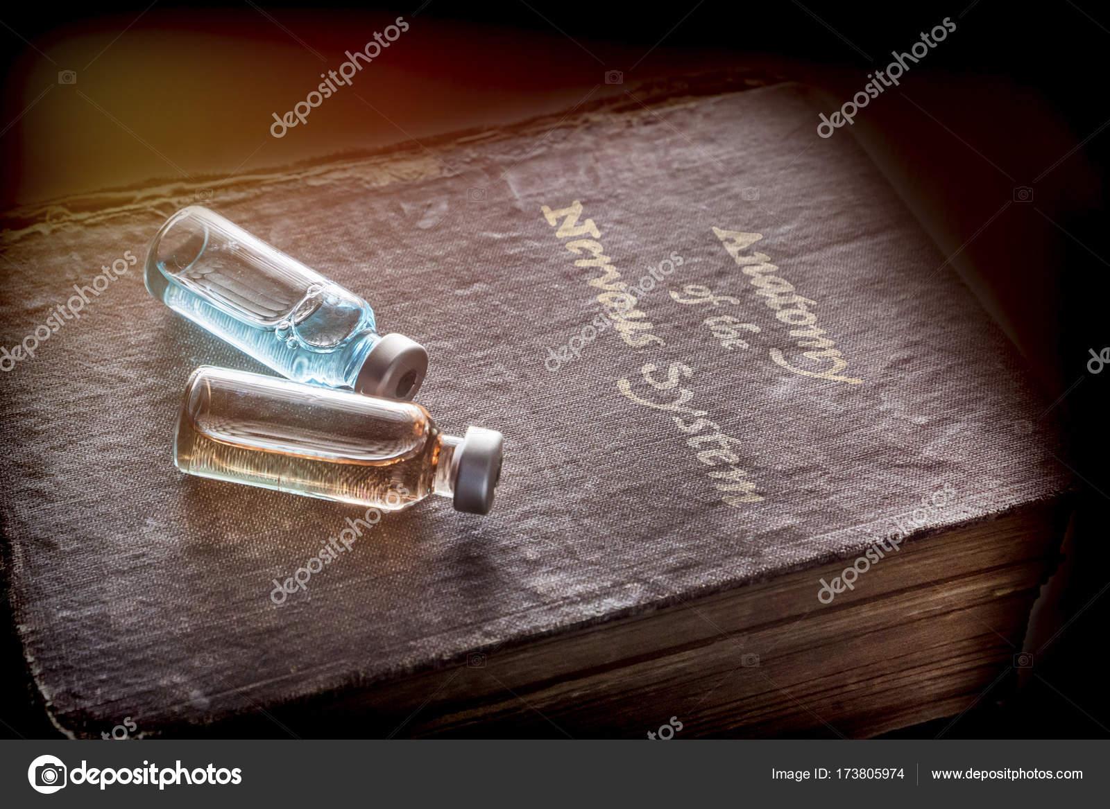 Zwei Fläschchen der Medizin auf ein altes Buch der Anatomie des ...