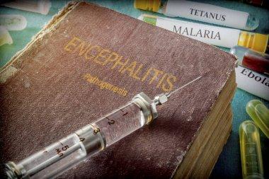 Vintage Syringe On A Book Of encephalitis, Medical Concept