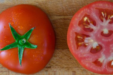 Perfect juicy fresh red tomato with green leaves in water droplets in a cut on a board