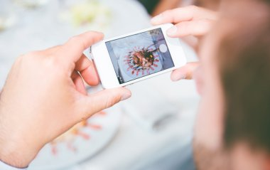 Man photographing food with smartphone